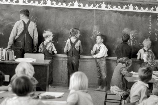 Chalk Board Math: February 1942. Third grade classroom at Weslaco, Texas by Arthur Rothstein. The rather 'large' fellow on the left caught my eye which suggests that this must have been a one room schoolhouse. Boys wearing overalls and the only two sets of feet are barefooted. Also it appears that the 2nd & 3rd boys from left are trying to help the 4th boy with his math. Lots going on in this classroom.