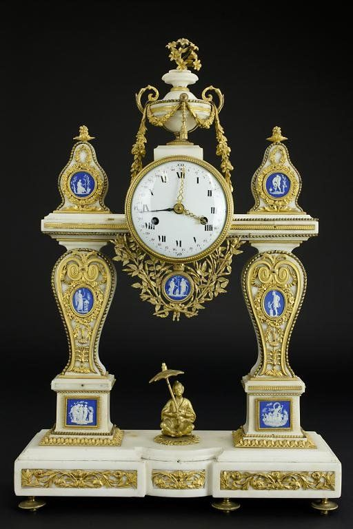 MARBLE, PORCELAIN AND GILTBRONZE MANTEL CLOCK : White marble fixture with elaborate gilt bronze foliate decorations all over. Seven small porcelain reliefs depict various Greek gods. Beautifully reticulated clock hands. Clock face with Roman numerals. With a bronze man sitting in the center of the mantel fixture holding an umbrella. H: 24 5/8 in. L: 16 1/2 in. W: 5 1/2 in.
