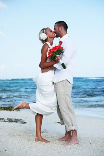 Casual beach wedding attire.  Khaki and white for the groom, simple white dress for the bride.