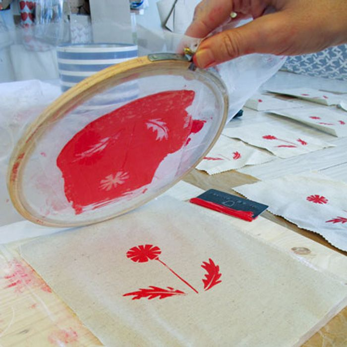 Small scale silk screen printing. Get an embroidery hoop, some silk, a