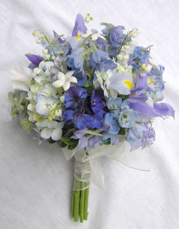 Blue wedding bouquet idea that includes pale iris, delphinium, lily of the valley from the garden, and hydrangeas.