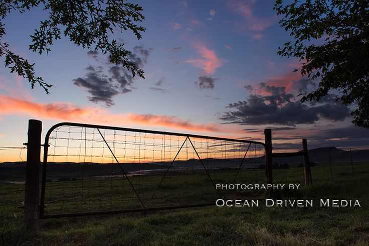 A farm gate with a spectacular sunrise in the background