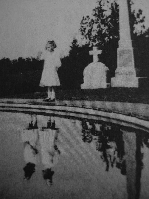1925 - a girl visiting the grave of her twin sister who died in a house fire the year before. Parents of the girl saw her, on many occasions, talking to her sister like she was playing in her room, but saw no one , until this photo was developed ... oooh