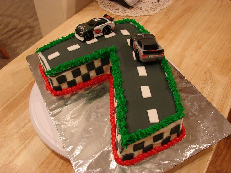 Race Car Birthday Cake - Racing themed cake for a little boy turning 7 at a local shelter.  Cake is chocolate, buttercream frosting and fondant decorations.  Cars are toys for him to keep after the cake is gone.  Got the idea from other cakes on CC.  TFL!