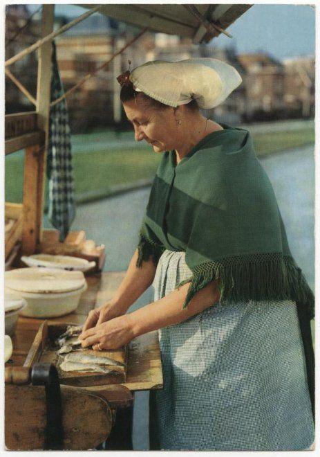 Scheveningse vrouw in klederdracht ( 'Door de weekse dracht') maakt vis schoon vermoedelijk op de Badhuisweg. ca 1960 Weenenk & Snel, NV v/h, Oosterhout #ZuidHolland #Scheveningen