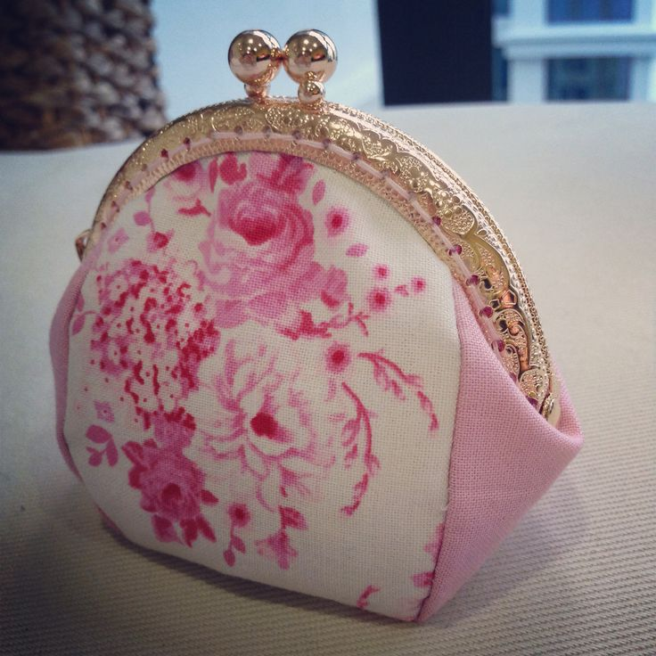 Pink floral purse with golden metal frame.