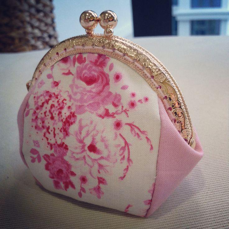 Pink floral purse with golden metal frame.