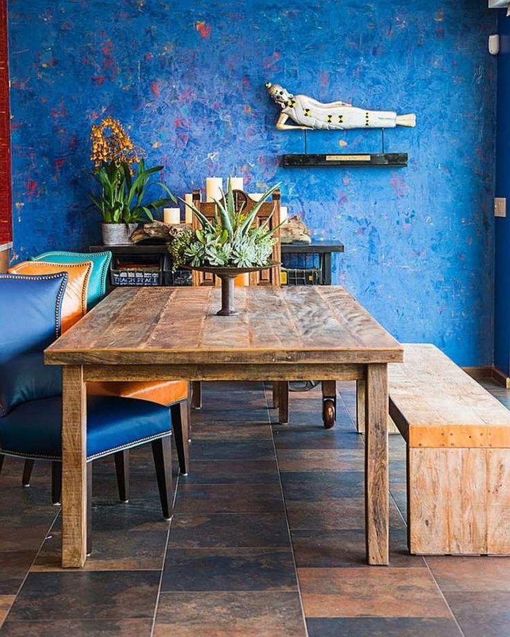 peinture murale bleu cobalt, table à manger en bois brut et banc assorti