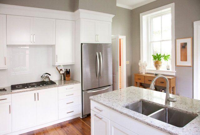 une plante verte et des accessoires métalliques dans la cuisine blanche