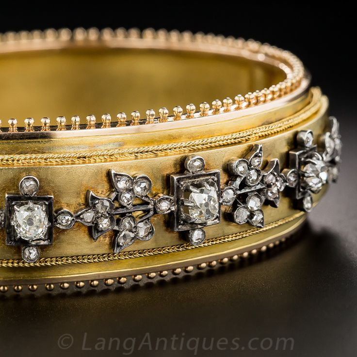 French Antique Diamond Bangle Bracelet. Ooh-la-la! From 19th-century France comes this regal and exquisite hinged bangle bracelet, superbly hand-fabricated in rich, velvety 18 karat yellow gold and overlaid with a fanciful foliate design rendered in contrasting silver and sparkling with 1.25 carats of bright old mine and rose-cut diamonds. The 3/4 inch wide bracelet is bordered all around with a finely beaded edge and is a full 7 inch bracelet size.