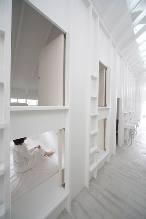 Ladders lead to capsule-sized bedrooms in Koyasan Guesthouse by Alphaville Architects.