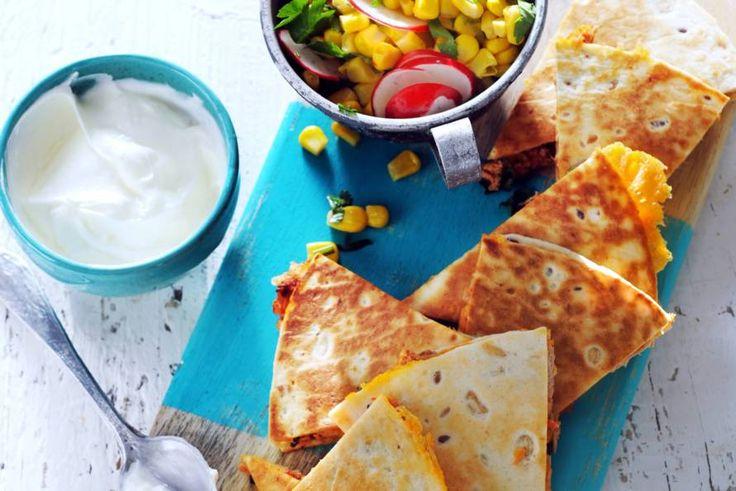 Twee krokant gebakken tortillawraps op elkaar met een smeuïge vulling van tonijn en cheddar: van quesadilla's geniet je dubbel - Recept - Allerhande
