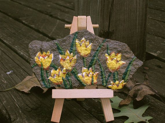 This painted tulips on stone with easel measures 5 inches long by 2 and 1/2 inches at the highest point. The miniature easel is made of wood and