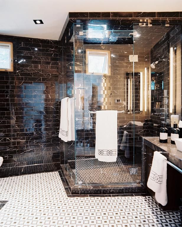 Contemporary Bathroom With Black Marble Tiled Walls: This stunning masculine master bathroom is tiled with St. Laurent marble. The floor is a mosaic of Thassos and St. Laurent marble tile. From HGTVRemodels.com