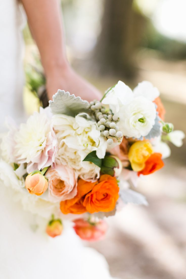 a gorgeous florida inspired bride's bouquet of peach cafe au lait dahlia, peach, white and pink ranunculus, white peony, peach garden roses, dusty miller and silver brunia.