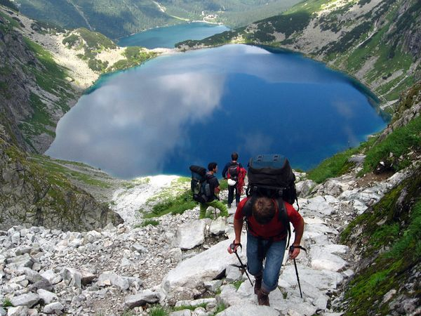 Hikers in the Tatra Mountains climb a trail above the twin pools of Black Tarn and Sea Eye Tarn. The highest point in the Carpathians, the mountains lie in Poland and Slovakia and are distinguished by their high-altitude lakes and well-marked trails.