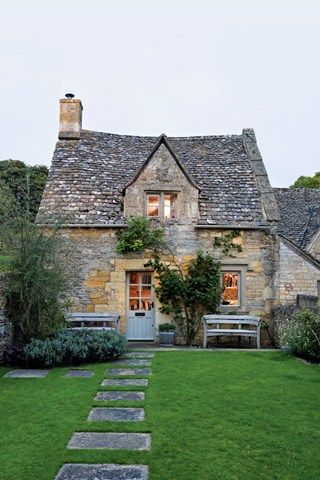 A stone path leads through the front garden to the main entrance of the Cotswolds cottage.