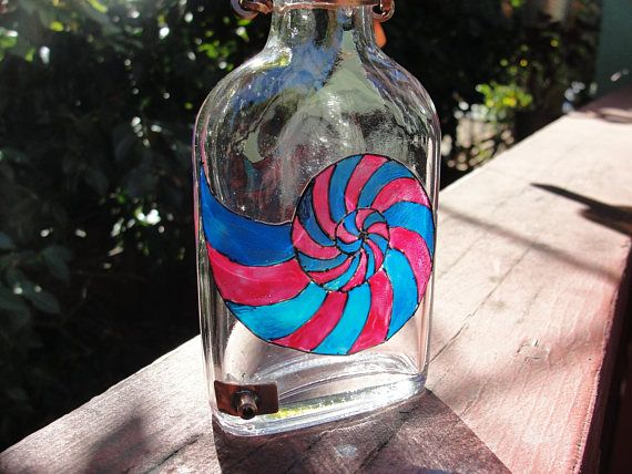 Gorgeous handmade hummingbird feeder made from up-cycled glass bottle and copper. A Nautilus design has been painted by hand using a unique glass paint which is baked on for permanency. This paint is translucent, similar to stained glass, and looks very pretty when the sunlight shines through. WHY OUR FEEDERS WORK SO WELL AT FEEDING HUMMINGBIRDS: Our sturdy hand-soldered copper spout is short in length, which allows the hummingbirds sugar water to be readily accessible. Longer spouts often…