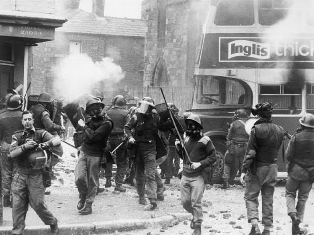 Soldiers wearing respirators while on riot control in the Catholic Falls area of Belfast. Broken glass litters the ground and a cloud of CS gas hangs in the air after a night of rioting, July 1970
