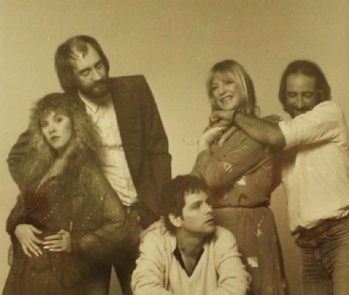 John McVie playfully choking Christine, a nonplussed Lindsey & Stevie & Mick