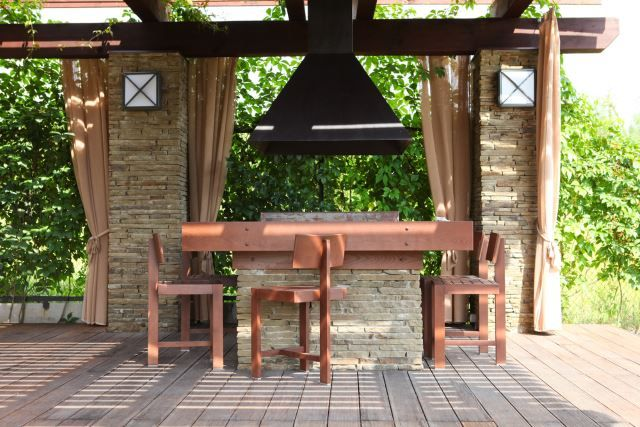 This is a great setup if you like to entertain outdoors. The covered patio area has a permanent table and chair setup that is not only adorable, but highly functional. The brick table will withstand the elements and looks great matching the scenery. What appears to be a massive light fixture hangs above the table, giving it a modern look with added usefulness. This would be a great setup for an outdoor lunch or barbecue with friends.