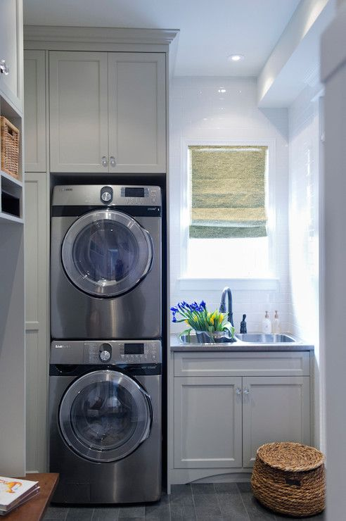 laundry / mud room combo with gray shaker cabinets, painted Benjamin Moore Paper Clip, accented with crystal pulls alongside a gray counter which frames the dual basin sink with oil rubbed bronze faucet below window highlighted by a subway tile backsplash and woven shade. A stackable front load washer and dyer stand beside the window across from mud room built-ins over gray tiled floors.