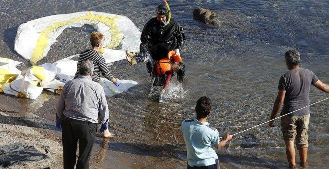 Un guardacostas griego saca del agua el cadáver de un niño refugiado en la costa griega de Lesbos. REUTERS/GIORGOS MOUTAFIS