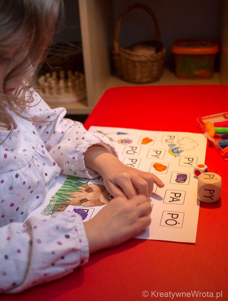 Dziecko rzuca obydwoma kośćmi i na karcie pracy wyszukuje i odczytuje sylabę jaką wylosowało, a następnie przykleja na nią plastelinę w takim kolorze jaki wylosowało.