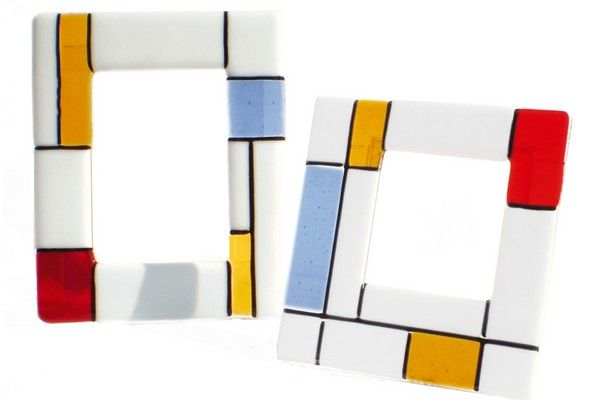 "Murano glass fusing photo frame. Composition characterized by the well known leitmotif that harks back to the modern art of Mondrian. White opalescent emphasizes brilliance of coloured inserts, while black chopsticks define geometry. This object is made entirely by hand and is therefore a unique piece, it can thus submit variations in color shades and in choosing the type of ""murrine"". This guarantees the originality and quality of craft product Made in Italy."