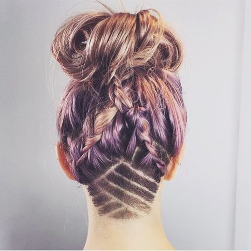 messy braids and bun hairstyle with shaved nape design: