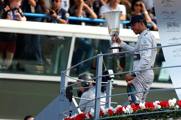 Race winner Lewis Hamilton (GBR) Mercedes AMG F1 with his trophy and champagne on the podium. Formula One World Championship, Rd13, Italian Grand Prix, Monza, Italy, Race Day, Sunday, 7 September 2014