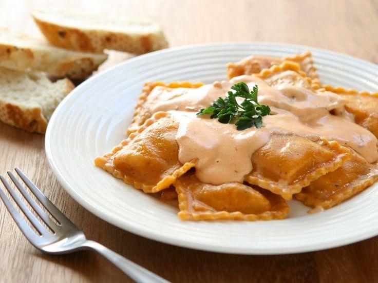 I ravioli di pesce sono un primo piatto con ripieno di salmone affumicato e gamberetti conditi con della panna macchiata con del pomodoro