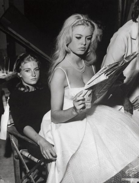 Brigitte Bardot reads a newspaper while perched on the lap of a friend