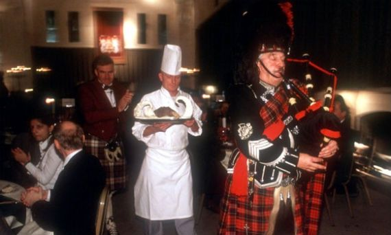 A piper in full Highland dress pipes in the haggis during a Burns' Night celebration at Stirling Castle