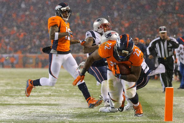 Running back C.J. Anderson #22 of the Denver Broncos scores a fourth quarter touchdown past cornerback Duron Harmon #30 of the New England Patriots at Sports Authority Field at Mile High on November 29, 2015 in Denver, Colorado.