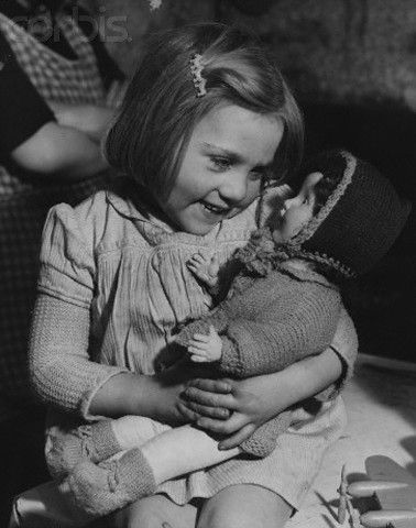 Happiness lights young Diana Burls face as she cradles her first Christmas present. The three-year-old, born in England during a World War II blitz, is one of the fortunate recipients of festive parcels sent from Australia. London, 1946.