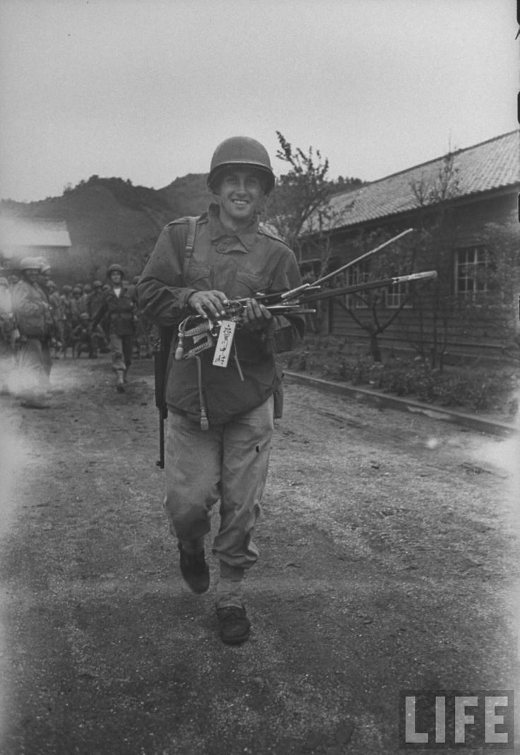 American Marine carrying several swords relinquished by Japanese officers during the surrender of Kurihara Naval base. Location: Onomichi, Honshu, Japan Date taken: September 1945 Photographer: Carl Mydans © Time Inc.