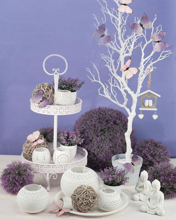 Etagere mit Lavendel, Windlichter und Schmetterlingen. Im Hintergrund Moosflechtkugeln.