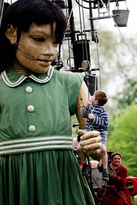 La petite géante promène un enfant sur sa main. (Ici, à Londres) - Compagnie Royal de Luxe
