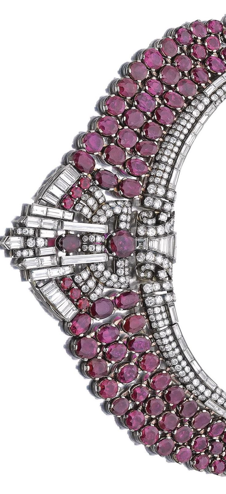 Ruby and diamond necklace, late 1930s.The necklace set with circular-, single-cut and baguette diamonds, suspending articulated oval ruby fringes, to the stylised scroll motifs, length approximately 385mm. | © 2014 Sotheby's