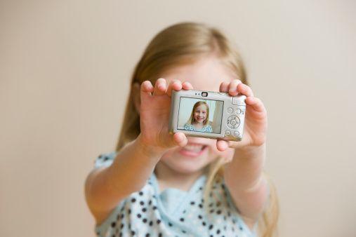 Girl holding digital camera with self-portrait