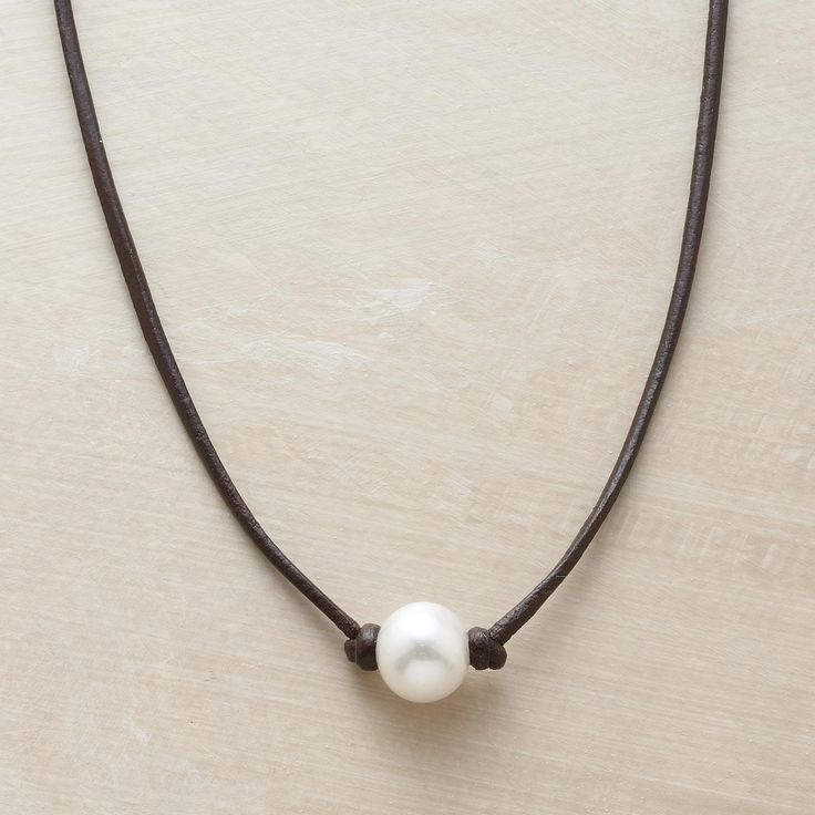 """ENCHANTED PEARL NECKLACE--Simply knotted on a leather strand, a cultured pearl's inborn luster becomes all the more enchanting in a handmade pearl necklace by Rebecca Lankford. Sterling hook and leather loop closure. Handmade in USA. 16""""L."""