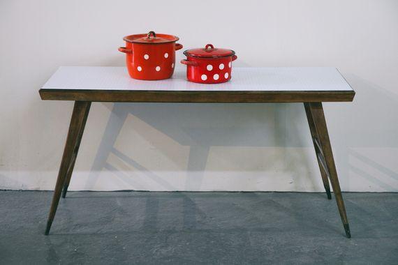 שולחן סלוני משנות ה50. הצבע המקורי של העץ חודש, פלטת השולחן שהיתה מצופה פורמייקה מיושנת, צופתה בטפט רהיטים בגוון תכלת לבן שמוסיף שיק, ייחודיות וקסם  -  ויחד עם זאת פרקטי ושימושי. פריט אחד ויחיד.