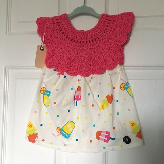 6-12 month size handmade baby girl dress with crochet top in pink yarn with white & colourful popsicle pattern cotton fabric skirt, fastened at the back with a button. Lightweight and pulls over the head.