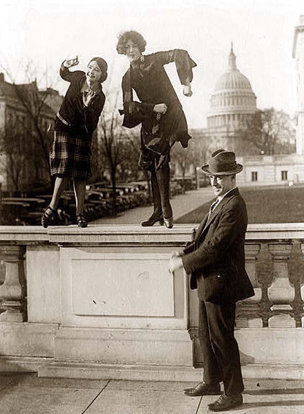The 1920's, two women dancing the Charleston on a railing in front of the US Capitol.