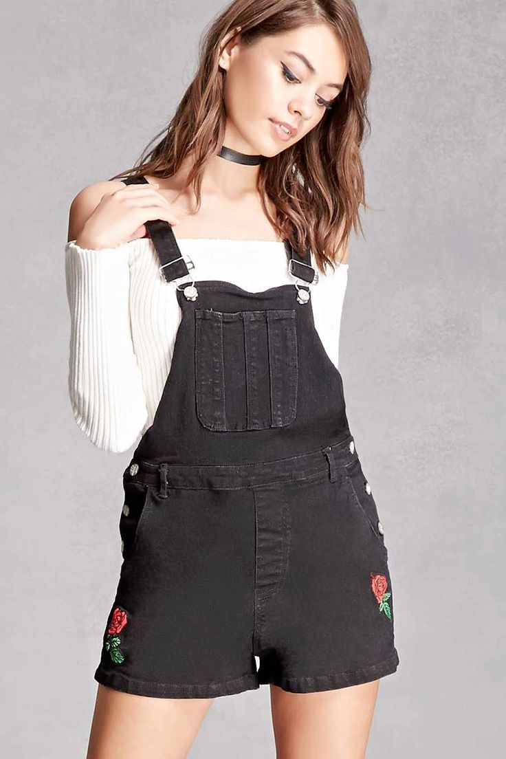 A pair of stretch-knit denim overalls by Motel™ featuring a rose embroidery on both sides, a square neck and back, adjustable shoulder straps with slide-lock closure, a front chest pocket, button sides, and a four-pocket construction.
