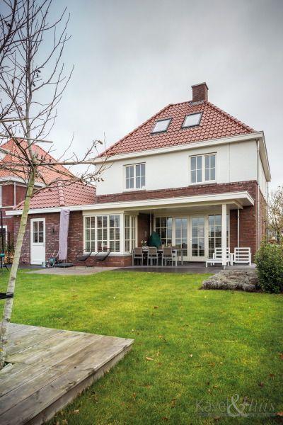 Klassieke woning, jaren-dertig woning. Rode pannen, rode bakstenen,  een wit element op de voorgevel. Grote tuin.