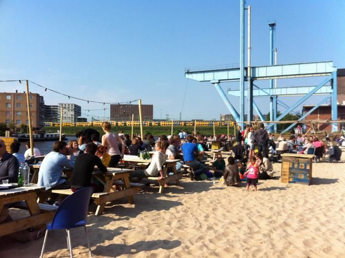 """Amsterdam Roest - Awesome Venue & city beach! Harbour side  PS: Roest can be a little difficult to find if it is your first time there. We recommend heading northeast on Czar Peterstraat if coming by bike (or tram 10) from the center of Amsterdam. Before you get to the train tracks, go left and follow the parking lots around until you reach Roest. The """"street address"""" is not exactly correct as Roest is not located on Czar Peterstraat but is situated on the water by the VOC Kade. If you can't…"""