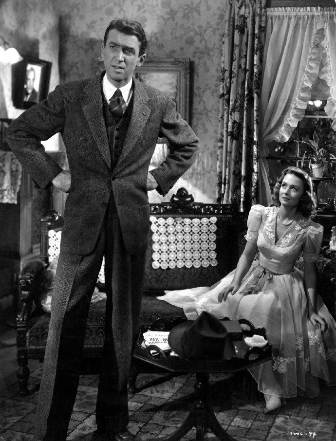 """A still featuring James Stewart and Donna Reed in It's a Wonderful Life (1946). Playing George Bailey, Stewart keeps his style professional in a three-piece tweed suit. """"An angel helps a compassionate but despairingly frustrated businessman by showing what life would have been like if he never existed."""""""