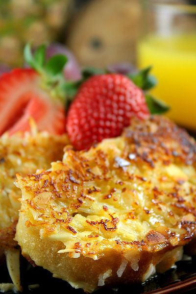 YUMMMM...Coconut French Toast.   1 large egg,  ¾ cup of coconut milk,  1 tablespoon sugar,  ½ teaspoon vanilla,  6 slices of stale baguette, sweetened shredded coconut, chopped almonds, 1 teaspoon butter, maple syrup, sugar, jam, fresh fruit.
